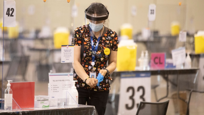 A health-care worker removes her protective gloves after sanitizing a workstation before doors open at a COVID-19 vaccine centre in Toronto on Friday, July 23, 2021. THE CANADIAN PRESS/Chris Young