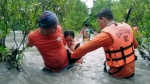 In this photo provided by the Philippine Coast Guard, residents wade along floodwaters as they are evacuated to safer grounds in Naujan, Oriental Mindoro province, central Philippines on Friday July 23, 2021. (Philippine Coast Guard via AP)