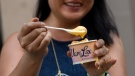 A woman enjoys the new macaroni and cheese flavour near Union Square in New York City on July 14. (aAexi Rosenfeld/Getty Images)