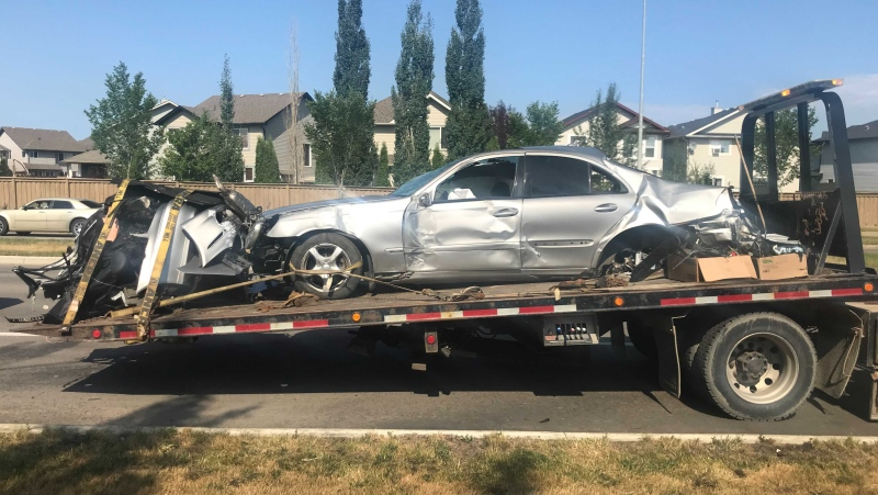 A tow truck hauls the Mercedes E320 away from the scene of a fatal accident on Rabbit Hill Road near MacTaggart Drive (CTV News Edmonton/Galen McDougall)