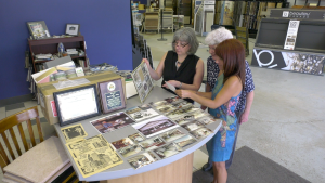 Catherine Maggio-Howley, left, Alice Maggio, centre, and Shelley Maggio reminisce over photos of the business. (Nate Vandermeer / CTV News Ottawa)