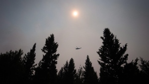 Smoke obscures the sun as a helicopter carrying a bucket battles the Gustafsen wildfire near 100 Mile House, B.C., on Saturday July 8, 2017. THE CANADIAN PRESS/Darryl Dyck