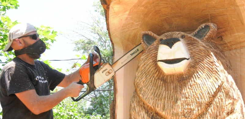 Chainsaw artist Dale Ruff carves a memorial to a bear that ran loose in a Dorval neighbourhood before being captured and euthanized on July 24, 2021. (Stephan Giroux, CTV News)