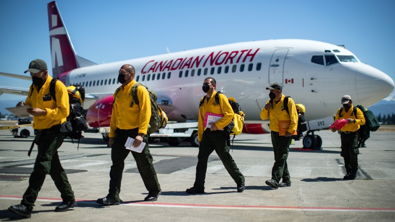 Firefighters from Mexico walk across the tarmac after arriving on a charter flight in Abbotsford, B.C, on Saturday, July 24, 2021. Ninety-nine firefighters will assist B.C. as the province deals with hundreds of wildfires burning in the province. They will undergo rapid COVID-19 testing and then be deployed to the interior of the province where they will stay in several bubbles separate from the more than 3,000 firefighters already working. THE CANADIAN PRESS/Darryl Dyck