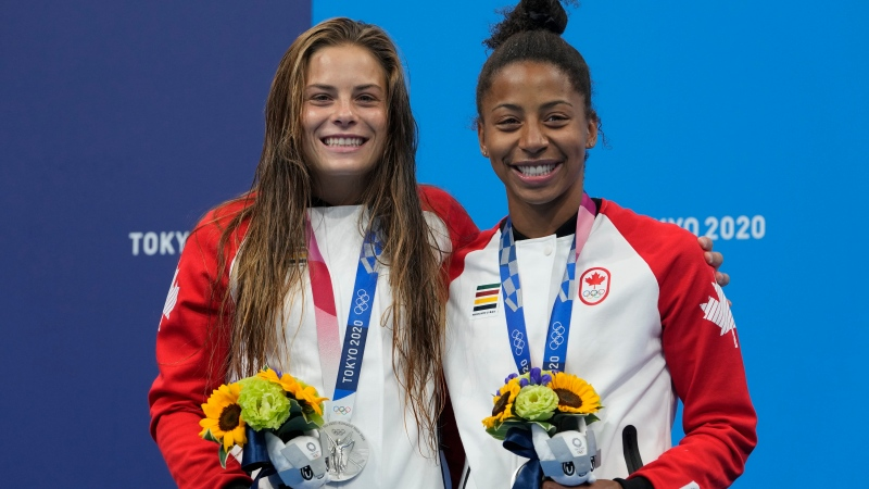 Jennifer Abel and Melissa Citrini Beaulieu of Canada pose for a photo after winning silver medals during the Women's Synchronized 3m Springboard Final at the Tokyo Aquatics Centre at the 2020 Summer Olympics, Sunday, July 25, 2021, in Tokyo, Japan. (AP Photo/Dmitri Lovetsky)