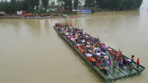 Rescuers use a motorized raft bridge to evacuate residents from a flooded rural area in Xinxiang in central China's Henan Province, Friday, July 23, 2021. (Chinatopix via AP)