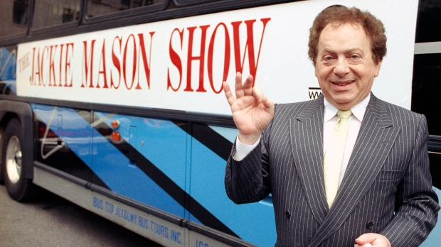 Actor/comedian Jackie Mason stands beside a bus displaying a sign advertising his TV show, 1992. Mason, a rabbi-turned-jokester whose feisty brand of standup comedy got laughs from nightclubs in the Catskills to West Coast talk shows and Broadway stages, has died. He was 93. Mason died Saturday, July 24, 2021, in Manhattan, the celebrity lawyer Raoul Felder told The Associated Press. (AP Photo/File)