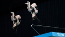 Meaghan Benfeito and Caeli McKay of Canada perform a dive during the women's synchronized 10-meter platform preliminaries at the FINA Diving World Cup Sunday, May 2, 2021, at the Tokyo Aquatics Centre in Tokyo. (AP Photo/Eugene Hoshiko)