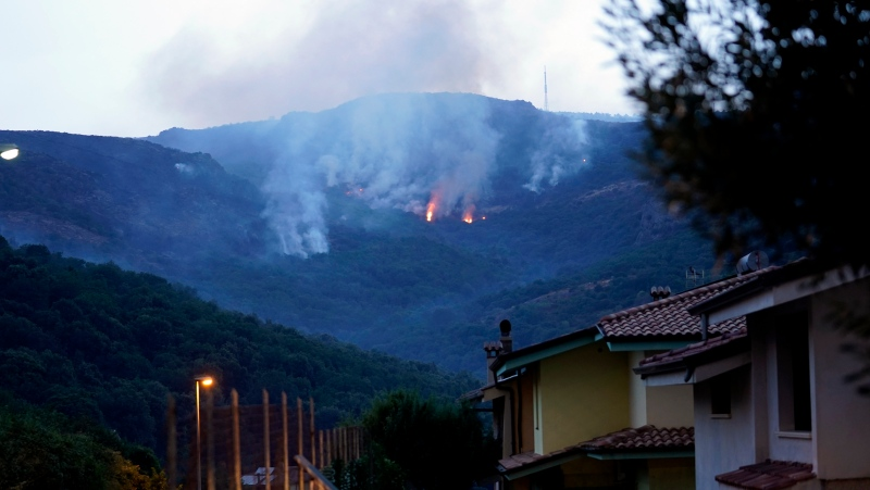 Fires rage through the countryside in Cuglieri, near Oristano, Sardinia, Italy, early Sunday, July 25, 2021. Hundreds of people were evacuated from their homes in many small towns in the province of Oristano, Sardinia, after raging fires burst in the areas of Montiferru and Bonarcado. (Alessandro Tocco/LaPresse via AP)