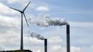 Chimneys of a coal-fired power plant smoke beside a wind turbine in Gelsenkirchen, Germany, Thursday, April 22, 2021. (AP Photo/Martin Meissner)