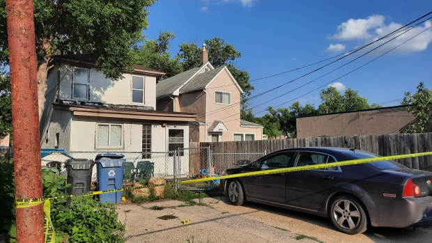 A house in the 400 block of Toronto Street is taped off with evidence markers visible on the ground as Winnipeg police investigate the death of a Winnipeg man on July 24, 2021.  (Source: Dan Timmerman/ CTV News Winnipeg)