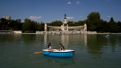 Women sail a boat during a hot day of summer at the Retiro park in Madrid, Spain, Wednesday, July 29, 2020. (AP Photo/Manu Fernandez)