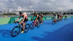 Left to right, Jonathan Brownlee of Great Britain (54), Kenji Nener of Japan (30),Vincent Luis of France (7), Marten van Riel of Belgium (27), Henri Schoeman of South Africa (51), Tyler Mislawchuk of Canada (15), Vincent Luis of France (7), Jonas Schomburg of Germany (4) and Dmitry Polyanskiy of the Russian Olympic Committee (8) copse the lead group during the cycling leg of the men's individual triathlon at the 2020 Summer Olympics, Monday, July 26, 2021, in Tokyo, Japan. (AP Photo/Jae C. Hong)