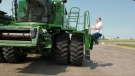 Matthew Almusa climbing into a combine at his work South Country Equipment in Emerald Park. (Kaylyn Whibbs / CTV News)