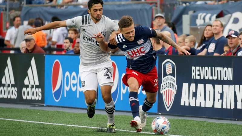 CF Montreal midfielder Mathieu Choiniere (29) and New England Revolution midfielder Arnor Ingvi Traustason (25) battle for the ball along the sideline during the second half of an MLS soccer match, Sunday, July 25, 2021, in Foxborough, Mass. (AP Photo/Mary Schwalm)