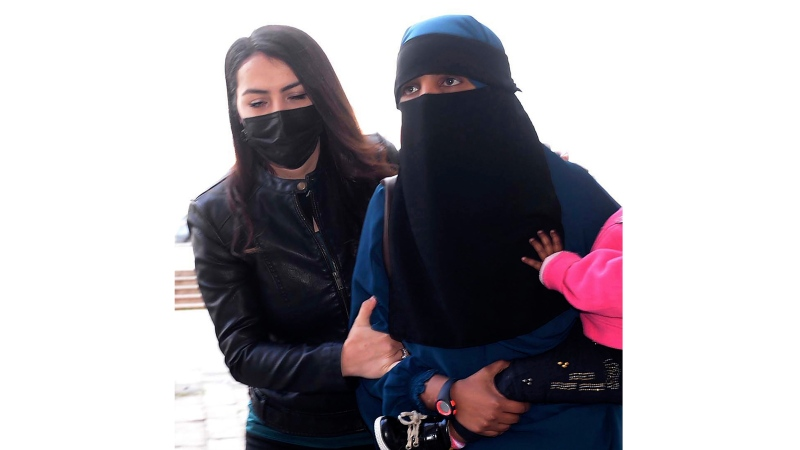 In this Feb. 15, 2021, file photo, a woman, who was identified only by her initials S.A., one of three New Zealand nationals, is escorted by a Turkish police officer, left, to the local courthouse in Hatay, Turkey. (DHA via AP, File)