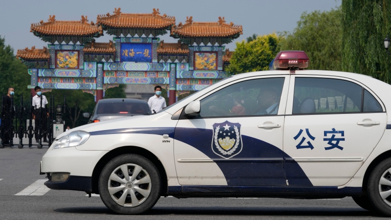 A police car passes by the entrance into the Tianjin Binhai No. 1 Hotel where U.S. and Chinese officials are holding talks in the Tianjin municipality in China on Monday, July 26, 2021. (AP Photo/Ng Han Guan)