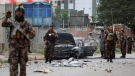 Security personnel inspect a damaged vehicle which was firing rockets in Kabul, Afghanistan, Tuesday, July 20, 2021. (AP Photo/Rahmat Gul)