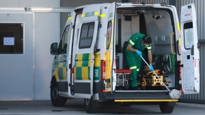 A paramedic cleans an ambulance after dropping off a COVID patient at the Brackengate Hospital of Hope, in Cape Town, South Africa, Wednesday, July 7, 2021. (AP Photo/Nardus Engelbrecht)