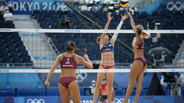 Kelly Claes, the United States and Tina Graudina, of Latvia, battle at the net as teammate Anastasija Kravcenoka looks on during a women's beach volleyball match at the 2020 Summer Olympics, July 26, 2021, in Tokyo, Japan. (AP Photo/Felipe Dana)