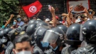 Protesters face Tunisian police officers during a demonstration in Tunis, Tunisia, on July 25, 2021. (Hassene Dridi / AP)