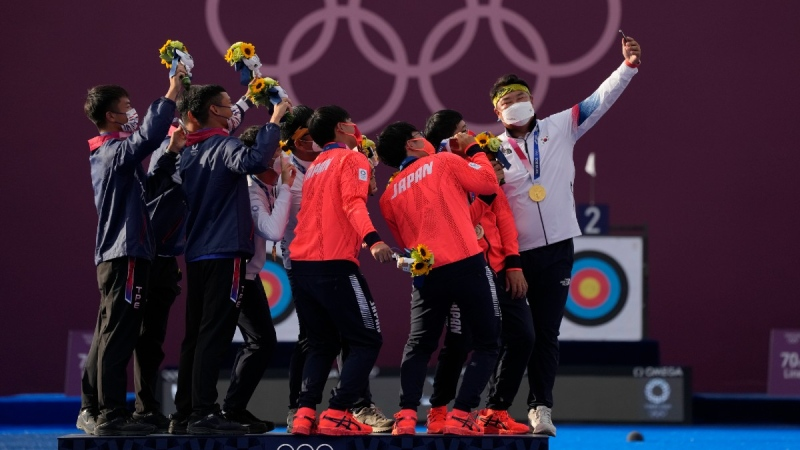 Medallists of Taiwan's team, second placed, Japan's team, third placed, and South Korea's team, first placed, take a selfie at the end of their medal ceremony at the 2020 Summer Olympics in Tokyo, on July 26, 2021. (Alessandra Tarantino / AP)