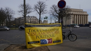 A banner reads « All united against political islamophobia » during a gathering in Paris, Sunday, Feb. 14, 2021. Activists rallied Sunday in Paris to demand that the French government abandon a bill aimed at rooting out Islamist extremism that the protesters say could trample on religious freedom and make all Muslims into potential suspects. (AP Photo/Thibault Camus)