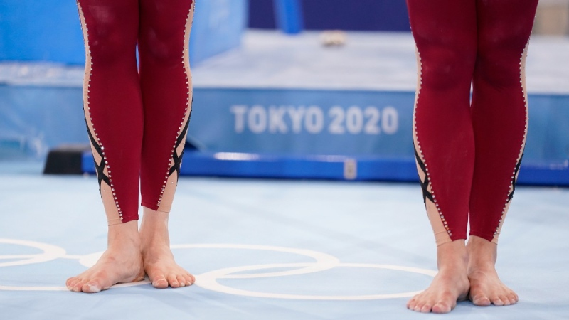 German gymnasts in unitard costumes wait to perform during the women's artistic gymnastic qualifications at the 2020 Summer Olympics, on July 25, 2021. (Ashley Landis / AP)