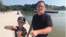Brandon Bastien, left, and his grandfather Steve Posthumus are seen with a catch while magnet fishing at Port Bruce, Ont. (Sean Irvine / CTV News)