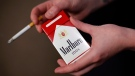 In this July 17, 2015, file photo, store manager Stephanie Hunt poses for photos with a pack of Marlboro cigarettes, a Philip Morris brand, at a Smoker Friendly shop in Pittsburgh. Phillip Morris International Inc. reports earnings Thursday, April 19, 2018. (AP Photo/Gene J. Puskar, File)