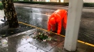A municipal worker clears a blockage in a roadside drain as Typhoon In-fa sweeps through Shanghai in China Sunday, July 25, 2021. Typhoon In-fa hit China's east coast south of Shanghai on Sunday after people living near the sea were evacuated, airline flights and trains were canceled and the public was ordered to stay indoors. (AP Photo/Chen Si)