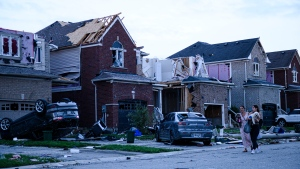 Residents leave their homes after a tornado caused significant damage, in Barrie, Ont., on Thursday, July 15, 2021. THE CANADIAN PRESS/Christopher Katsarov