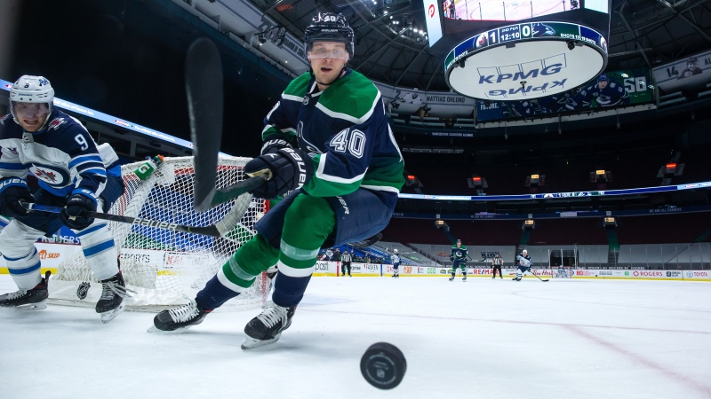 Vancouver Canucks' Elias Pettersson (40), of Sweden, reaches for the puck during the second period of an NHL hockey game in Vancouver, on Friday, Feb. 19, 2021. (Darryl Dyck  / THE CANADIAN PRESS)