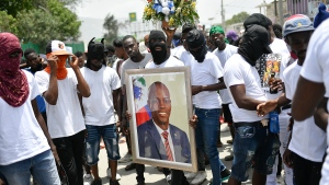 Members of the gang led by Jimmy Cherizier, alias Barbecue, a former police officer who heads a gang coalition known as 'G9 Family and Allies,' carry a photo of slain President Jovenel Moise during a march to demand justice for his murder, in La Saline neighborhood of Port-au-Prince, Haiti, Monday, July 26, 2021. (AP Photo/Matias Delacroix)