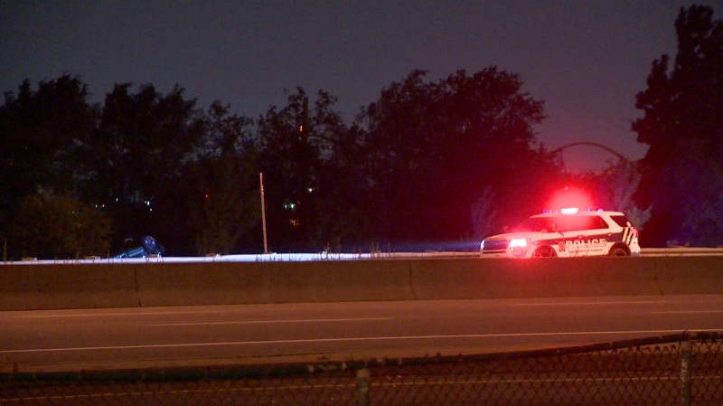 A police cruisier shines light on a flipped over car on the side of the road near the Jacques-Cartier Bridge following a police chase Monday, July 26, 2021. (Cosmo Santamaria/CTV News)