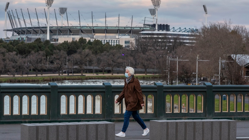 A woman wearing a mask walks along a bridge as she walks past the MCG (Melbourne Cricket ground) as lockdown due to the continuing spread of COVID-1 starts in Melbourne, Wednesday, Aug. 5, 2020. (AP Photo/Asanka Brendon Ratnayake)