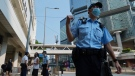 Police officers walk outside a court as they wait for Tong Ying-kit's arrival at a court in Hong Kong Tuesday, July 27, 2021. (AP Photo/Vincent Yu)