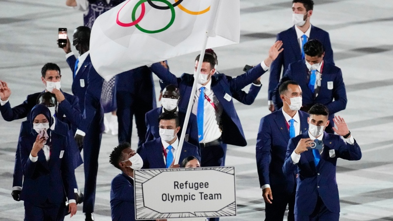 Yusra Mardini and Tachlowini Gabriyesos, of the Refugee Olympic Team, carry the Olympic flag during the opening ceremony in the Olympic Stadium at the 2020 Summer Olympics, Friday, July 23, 2021, in Tokyo, Japan. (AP Photo/David J. Phillip)