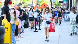 People shop and wait in long lines to enter stores along Queen Street West during the COVID-19 pandemic in downtown Toronto on Friday, June 11, 2021. THE CANADIAN PRESS/Nathan Denette