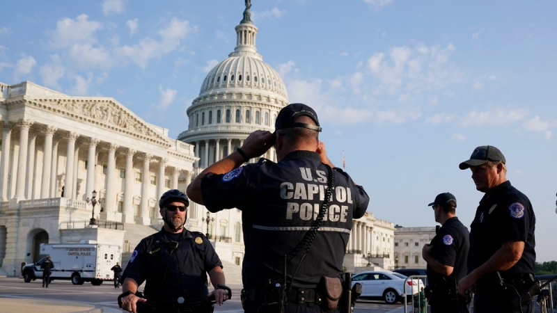 The U.S. Capitol is seen in Washington, as U.S. Capitol Police watch the perimeter early on July 27, 2021. (J. Scott Applewhite / AP)
