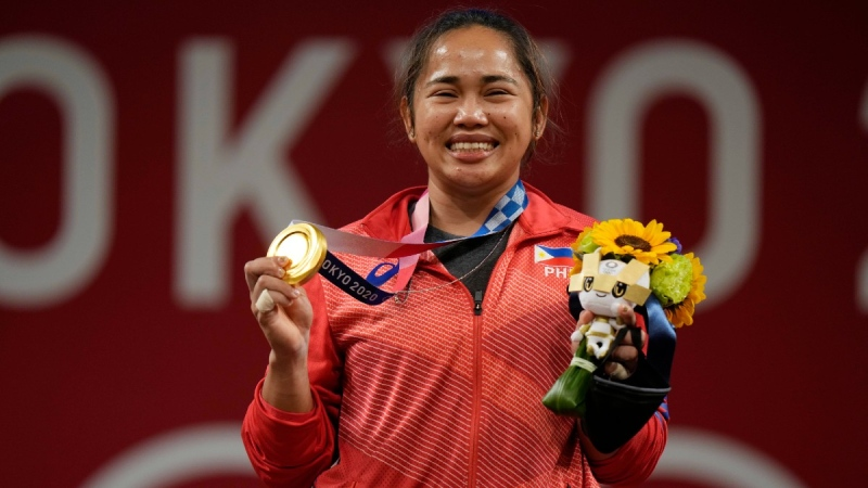 Hidilyn Diaz of Philippines celebrates on the podium after winning the gold medal in the women's 55kg weightlifting event in Tokyo, in July 26, 2021. (Luca Bruno / AP)