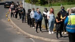 People queue to receive COVID-19 vaccinations at the ESSA Academy in Bolton, England, Tuesday May 18, 2021. (AP Photo/Jon Super)