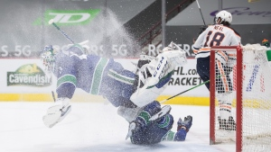 Vancouver Canucks' Matthew Highmore, bottom, crashes into goalie Braden Holtby (49) as Edmonton Oilers' James Neal skates behind them during the first period of an NHL hockey game in Vancouver, B.C., Monday, May 3, 2021. (Darryl Dyck / THE CANADIAN PRESS)