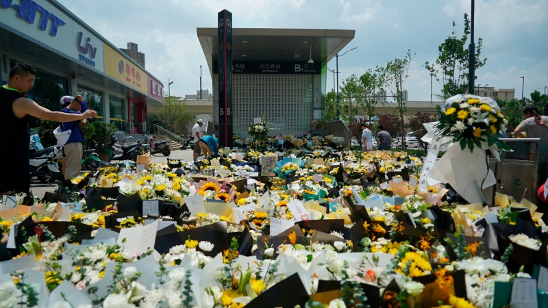 Bouquets of flowers are placed outside the entrance to a subway station in Zhengzhou in central China's Henan Province, Tuesday, July 27, 2021. Residents laid flowers on Tuesday at the entrance of the subway station where more than a dozen people died after a record-breaking downpour flooded large swaths of Henan province in central China. (AP Photo/Dake Kang)