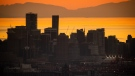The downtown Vancouver skyline is seen at sunset with English Bay and Vancouver Island in the distance, as seen from Burnaby Mountain on Saturday, April 17, 2021. (Darryl Dyck / THE CANADIAN PRESS)