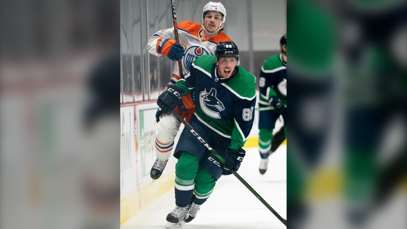 Vancouver Canucks defenceman Nate Schmidt (88) fights for control of the puck with Edmonton Oilers right wing Josh Archibald (15) during first period NHL action in Vancouver, Thursday, February 25, 2021. THE CANADIAN PRESS/Jonathan Hayward