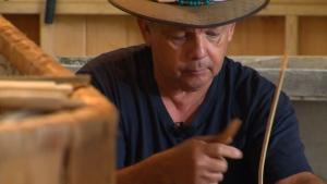 Todd Labrador is seen working on a birchbark canoe.