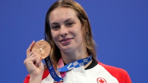 Penny Oleksiak of Canada holds up her bronze medal from the women's 200-meter freestyle final at the 2020 Summer Olympics, Wednesday, July 28, 2021, in Tokyo, Japan. (AP Photo/Matthias Schrader)