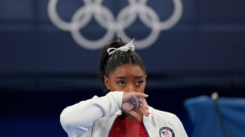 Simone Biles, of the United States, watches gymnasts perform at the 2020 Summer Olympics, July 27, 2021, in Tokyo. (AP Photo/Ashley Landis)