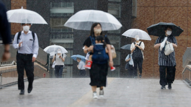 People make their way in a rain affected by a tropical storm in Sendai, Miyagi prefecture, northeast of Tokyo Wednesday, July 28, 2021. (Kyodo News via AP)